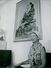 Smiling Mala Rubinstein sitting on the side of the room, 1965.