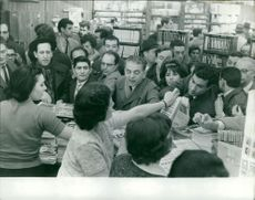 People purchasing newspapers inside a bookstore in Paris.  Taken - 23 Mar. 1962
