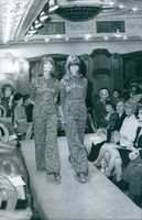 A photo of a Swedish fashion designer Katja of Sweden during a fashion show event while being watched by different organizers, designers and model.