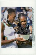 The sisters Venus and Serena Williams are kidding on a small dog sitting in the winning squad during the US Open.