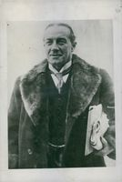 Stanley Baldwin photographed wearing a fur coat and carrying folders of papers.