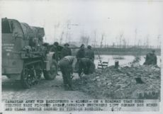 Canadian engineers lift German box and clear rubble caused by typhoon bombing.