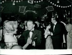 Kirk Douglas, Maria Schell, and Pascale Petit dancing at a party. 1961.