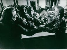 Mrs. Betty Ford handshakes Mrs. Rockefeller during a ceremony.