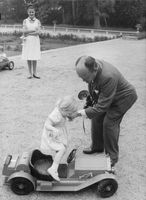 Man helping Princess Astrid getting into toy car.