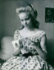 1962  Mireille Negro siting and holding pigeon.