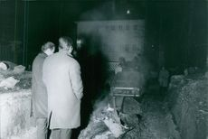 """People gathered in street at night and looking at a vehicle during the search and rescue efforts for Emmanuel Malliart.  """"Maillart's house during the kidnapping""""  1987"""