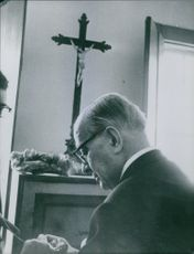 Georges Bidault is praying inside the chapel.
