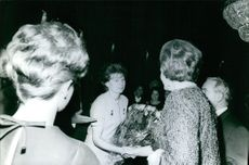 A lady is shaking hand with Russian cosmonaut Valentina Vladimirovna Tereshkova, while Valentina hold some flowers