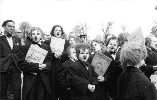 A group of men wearing joker's nose behaving like jokers and holding posters in their hands.