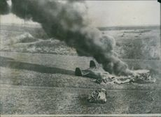 View of a crashed and burning airplane on the ground. 1940