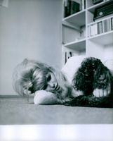 Vivi Bach lying on the floor with her pet dog.