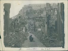 1914  A picture of a  soldier siting between destroyed and destructed house after bombardment in the war.
