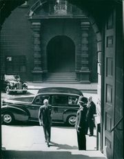 A political dignitary walks towards the doorway while looking at the man on the side making a salute, 1956.