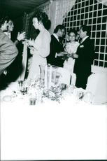 Princess Maria Gabriella talking to people around hie in a social gathering.
