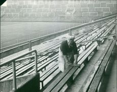 A Tibetan woman cleaning the bench for spectators in a stadium.