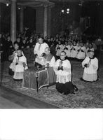 Pope Paul VI siting with people and praying to god in church.