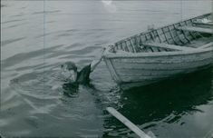 A man pulling his boat in the waters.