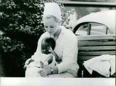Woman sitting on bench and carrying a baby.