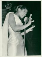 Eartha Kitt in beautiful light dress singing on stage