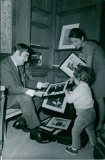 Pierre Salinger looking at the photographs with his wife and child.
