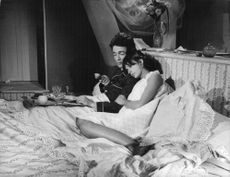 Jacques Charrier in bed with a woman in a movie scene holding a chicken wing in his hand.