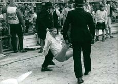 A soccer thug being lead off by police.