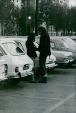 A couple having conversation in parking area.1973