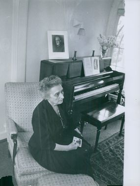 Professor Chretini sitting on a reclining chair by the piano at her house.