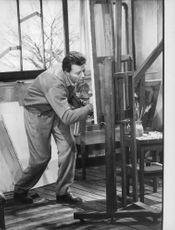Gerard Philipe painting on a drawing board.