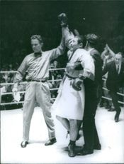 Referee raising hands of a winner boxer in the ring.