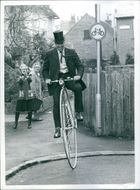 1972 Life is all ups and down. Woman surprised to see a man moving by a big wheel bicycle. Plain sailing once you are