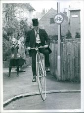 """1972 Life is all ups and down. Woman surprised to see a man moving by a big wheel bicycle. Plain sailing once you are """"aboard""""- But it wasn't easy at first."""