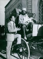 Richard Todd talking to a man on horse cart while visiting location of Cinecitta.