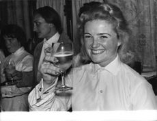 A woman showing drink glass on camera.