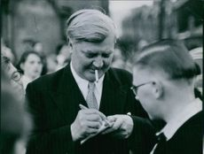 Aneurin Bevan, known as Nye Bevan, seen smoking a cigarette while signing autographs.