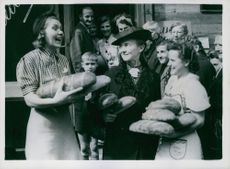 German women leaving a baker's shop with a triumphant smiles, carrying first loaves of white bread. August 22, 1945