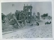 Inhabitants who have returned to battle-wrecked Valognes, circulate in the streets lined by rubble from houses destroyed in the severe war operations that marked the advance of Allied armies through the town.