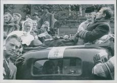 A man lying on stretcher placed on the roof of a car while people stood on the side.