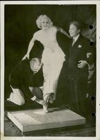 Actress Jean Harlow takes his footprint with the help of director Sid Grauman