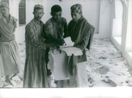 Men checking out some torn and old documents in a certain place cluttered with pieces pf papers in Yemen, 1962.