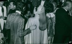 Men and women standing and gathered in different costumes. 1970