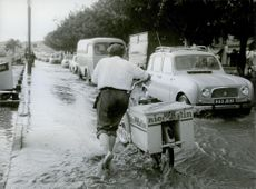A man pushing his bicycle on the flooded road in Paris. 1968