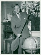 Thor Heyerdahl in his home with a paddle from Hervey Island
