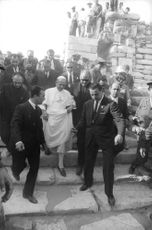 Pope Paul VI coming down from stairs with people.