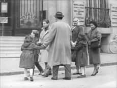 Roberto Rossellini standing with his family.