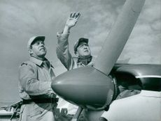 Two soldiers standing beside airplane, waving.