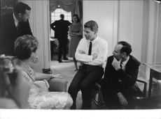 "Robert Francis ""Bobby"" Kennedy sitting on a hand rest while having a conversation."