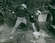 Two men fighting with each other at road side where the man and woman lying on the ground, a scene in a film