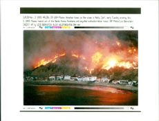 flames threaten homes on the ocean.